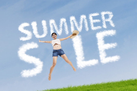 Excited woman jumping on the meadow with cloud design of summer sale sign photo