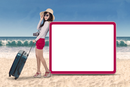 promotion girl: Young attractive woman standing next to copyspace. shot on the beach