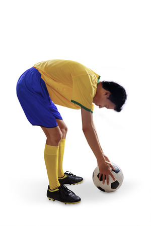 put: Brazilian soccer player put soccer ball on the floor. isolated on white