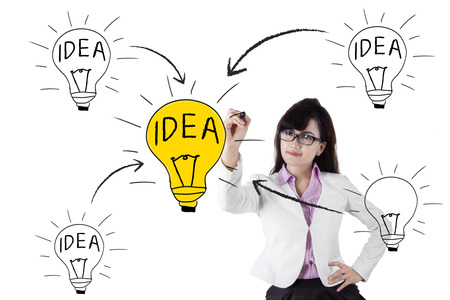 Business woman drawing light bulb with her black marker photo