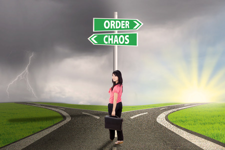 Businesswoman standing on the road with signpost of order and chaos photo