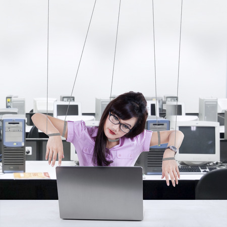 dominate: Portrait of businesswoman working at office controlled by strings