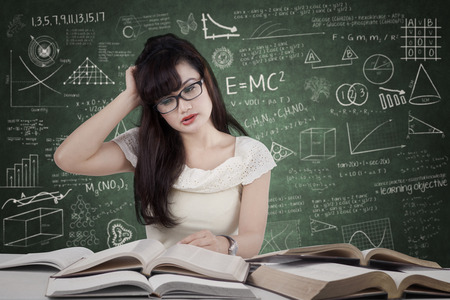 Confused female student reading many books for exam in the class photo