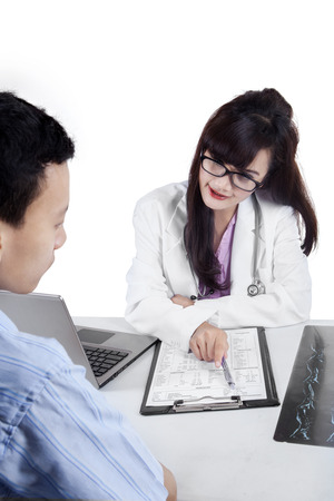 Female doctor explaining checkup result to her patient on clipboard photo