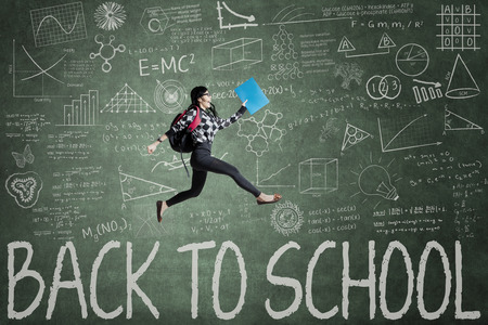 high spirits: Female student jumping in classroom through back to school text on blackboard