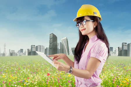 rural development: Asian young engineer using digital tablet outdoors Stock Photo