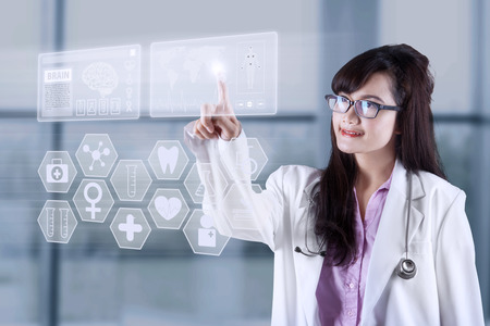 Female doctor touching medical interface with modern technology photo