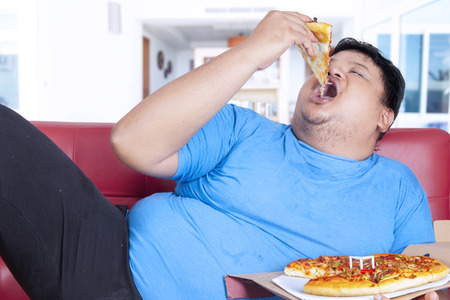 Obese person eats pizza while sitting on couch at home