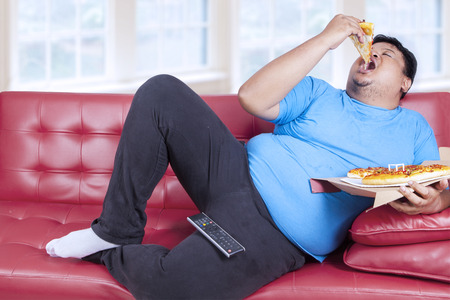 Overweight man eats pizza while sitting on couch at home photo