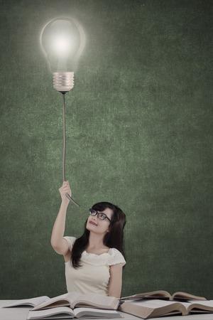 Retrato de estudiante inteligente colegio femenino con los libros y la bombilla de luz brillante sobre su cabeza como símbolo de las ideas brillantes