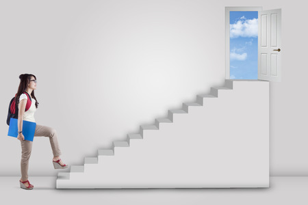 College student stepping up on stairs to the success door  photo