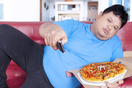 man mouth: Overweight man eats pizza while watching tv at home Stock Photo