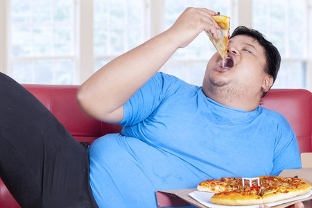 man mouth: Obese person eats pizza while sitting on couch at home