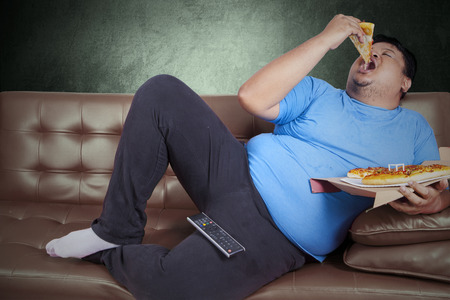 Obese person eats pizza while sitting on couch at home photo