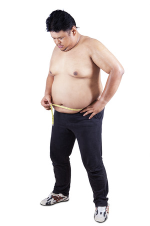 Obese person measuring his belly, isolated on white background photo