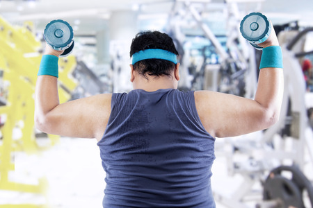 Fat man exercising with two dumbbells in the fitness center