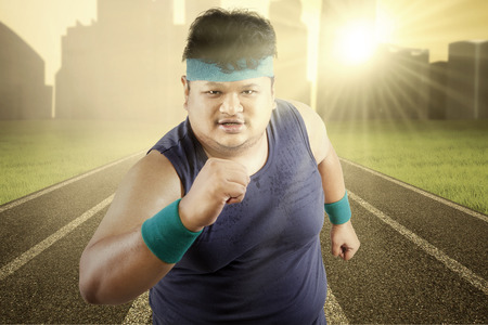 Fat man running for exercising on racing track Stock Photo