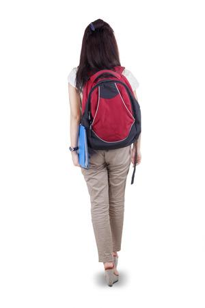 コンピューターの背面を歩いて、女子学生の白い背景で隔離 写真素材