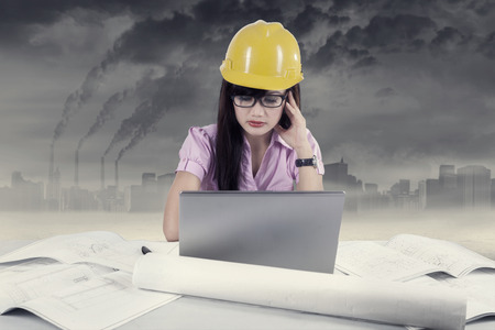 Stressful young architect working with laptop and blueprint photo