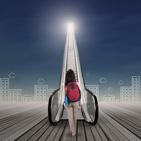 up stair: Bright future concept with female college student stepping up on the escalator