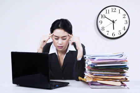 Asian businesswoman sitting in office, looking tired. photo