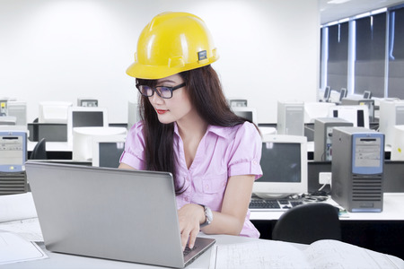 asian architect: Portrait of young asian architect working at office with laptop and blueprint Stock Photo