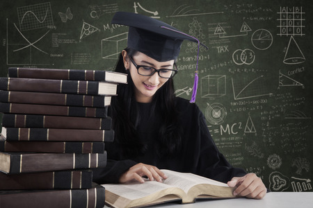 Happy student in graduation cap is reading books at classroom photo