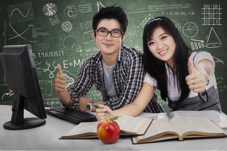 Happy student couple showing thumbs-up with computer on the desk photo