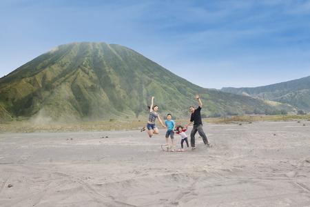 Joyful family jump on volcanic desert, shot outdoors photo
