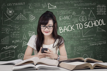 Female student using mobile phone in classroom photo