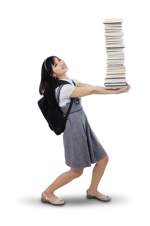 Attractive young female college student carrying a stack of books. photo