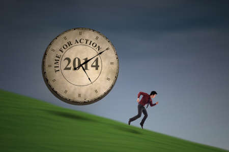 employe: Businessman is running with a big time clock chasing behind him on green field Stock Photo
