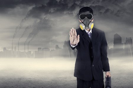 emission: Pollution concept: portrait of businessman in a gas mask warn to stop pollution