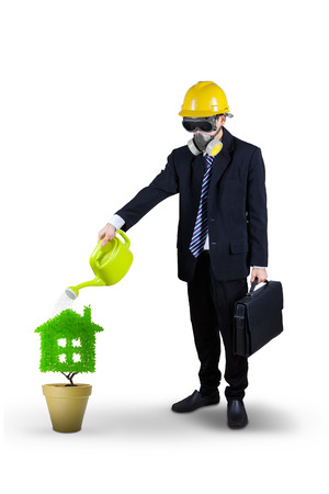 Businessman wearing a gas mask watering plant in pot with can. isolated on white background photo