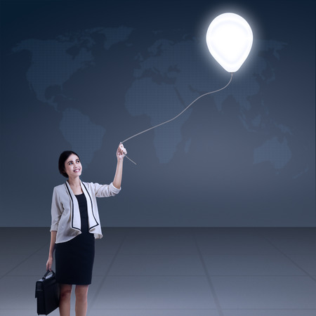 Young businesswoman holding bulb balloon with world map background photo