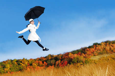 Young woman jumping with holding umbrella at autumn day photo
