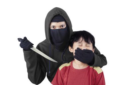scared child: Ni�o asustado con la mano de un hombre adulto que cubre la boca y amenazando con un cuchillo Foto de archivo