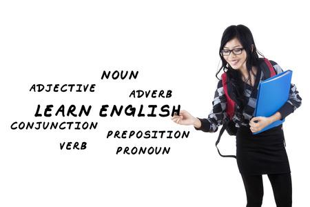 Female student writes english language materials on whiteboard photo