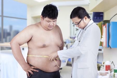 Doctor examining a patient obesity, shot in hospital Stock Photo