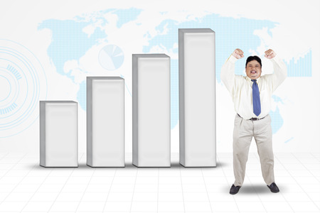 winning stock: Fat businessman celebrate his success while standing near to financial graph