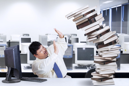 Businessman overworked with a pile of books in the office photo