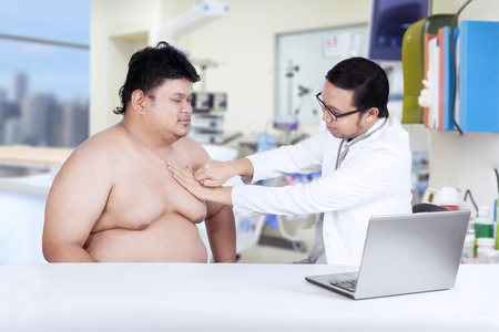 Doctor is checking a fat man. shot in the hospital photo
