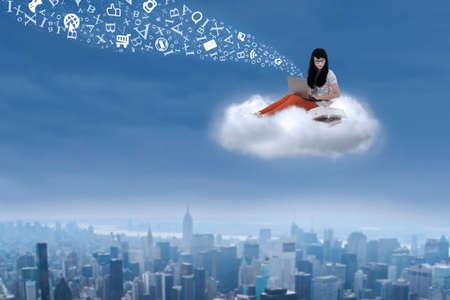 libros volando: Hermosa estudiante sentado en una nube sobre paisaje urbano con la computadora portátil y cartas de vuelo Foto de archivo