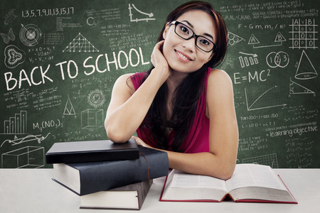 Smiling friendly female college student with textbooks.  Stock Photo