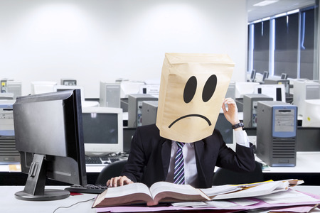 Stressful anonymous businessman scratching his head in office photo