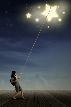 Portrait of young female college student taking stars from the sky space photo