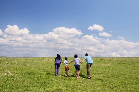 Happy family running together in meadow shot outdoor Stock Photo