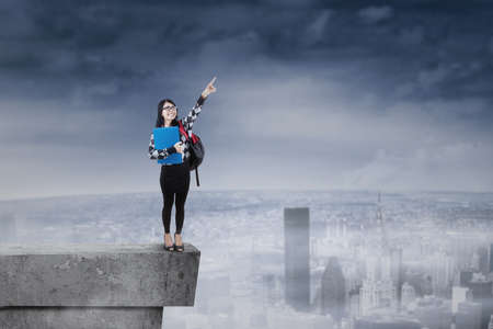 courageous: Female student standing on rooftop and pointing at sky Stock Photo