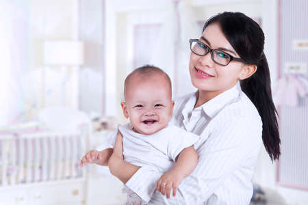 asian family home: Asian businesswoman and her baby, shot at home