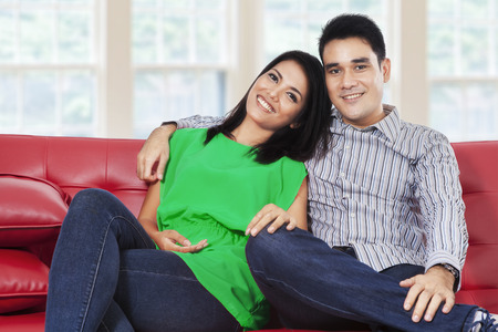 Happy young couple laughing and looking at camera in a living room photo